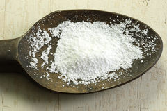 Powdered sugar. On a wooden spoon stock photo