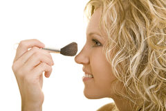 Powdering the nose. Blonde Woman applying powder to her nose royalty free stock photography