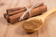 Powdery cinnamon and sticks on wooden table, seasoning for cooking Stock Photo