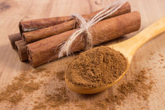 Powdery cinnamon and sticks on wooden table, seasoning for cooking Stock Photos