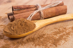 Powdery cinnamon and sticks on wooden table, seasoning for cooking Stock Photography