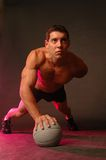 Power. Male doing a one armed pushup on a sports ball Royalty Free Stock Image