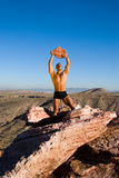 Power. Muscular man with tattoos, in underwear, lifting a big rock above his head. Rocky landscape in the background royalty free stock photo