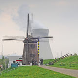 Power anachronism. Old windmill with nuclear cooling towers in the back, Antwerp, Belgium, Europe Royalty Free Stock Photography