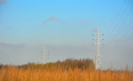 Power and anergy: electricity pylons in nature Royalty Free Stock Images