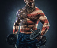 Power athletic bearded man in training pumping up muscles with d. Umbbell. The body is depicted an American flag. Concept: Captain America Royalty Free Stock Photo