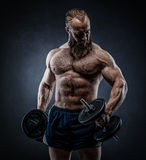 Power athletic bearded man in training pumping up muscles with d royalty free stock photos