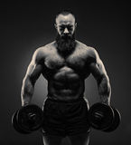 Power athletic bearded man in training pumping up muscles with Royalty Free Stock Images