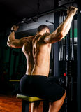 Power athletic guy bodybuilder, execute exercise with gym apparatus, on broadest muscle of back Royalty Free Stock Images