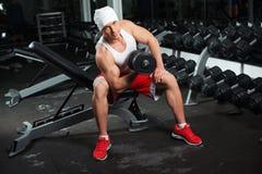 Power athletic guy bodybuilder, execute exercise Stock Photo