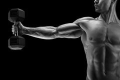 Power athletic man pumping up muscles with dumbbell. Close-up of a power fitness man's hand with dumbbell. Strong bodybuilder with six pack, perfect abs Stock Images