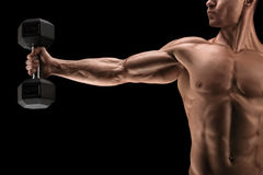 Power athletic man pumping up muscles with dumbbell. Close-up of strong bodybuilder with six pack, perfect abs, shoulders, biceps, triceps and chest, deltoids Royalty Free Stock Images