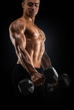 Power athletic man pumping up muscles with dumbbell. Handsome power athletic man in training pumping up muscles with dumbbell. Strong bodybuilder with six pack Royalty Free Stock Photo