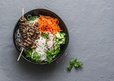 Power balanced buddha bowl. Asian style beef skewers, rice vermicelli, pickled vegetables salad carrots, cucumbers, radishes, herb Royalty Free Stock Photo