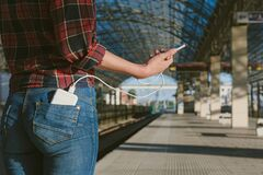 Power bank in the back pocket of the girl at the railway station, charges the phone, against the background of pyron, side view of