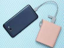 Power bank charged modern smartphone on creative blue background, top view. Power bank charged modern smartphone on creative blue background, top view royalty free stock images