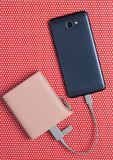 Power bank charged modern smartphone on a creative red background in polka dot, top view. Power bank charged modern smartphone on a creative red background in royalty free stock photo