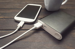 Power bank charging a smart phone next to a cup of coffee Royalty Free Stock Photo