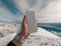 Power bank in hands. Tourist charges a devices in nature, against the backdrop of a winter mountains landscape stock photography