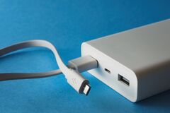 Power bank with micro usb cable in port on blue background