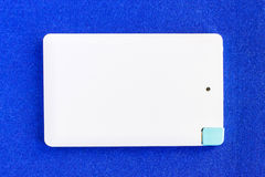 Power bank small mini size on blue background Royalty Free Stock Images