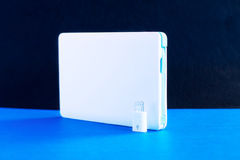 Power bank small mini size on blue background Stock Photos