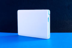 Power bank small mini size on blue background. Power bank small, mini size on blue background royalty free stock photography