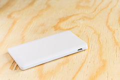 Power bank small mini size on wooden background. Power bank small mini, size on wooden background stock photos