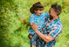 Power being father. Rustic family. Growing cute cowboy. Small helper in garden. Little boy and father in nature. Background. Spirit of adventures. Strong like stock photography