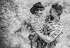 Power being father. Rustic family. Growing cute cowboy. Small helper in garden. Little boy and father in nature royalty free stock photo