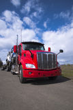 Power big rig red semi truck transporting another semi trucks on. A powerful modern big rig red semi truck carries other articulated lorry semi trucks of various Royalty Free Stock Images