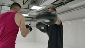 Power blow to boxing paw. Strong tattooed athlete in sports clothing training on boxing paws with partner. Slow motion: Power blow to boxing paw. Strong tattooed stock video