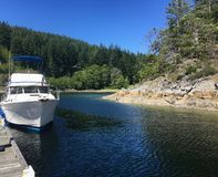 A power boat docked close to shore on a peaceful day on Cortes Island, Desolation Sound, British Columbia, Canada. Gorgeous Day stock photos
