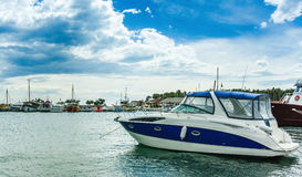 Power boat parked on the sea. The background is a beautiful blue sky and clouds stock photography