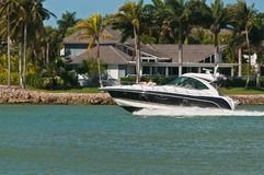 Power boat speeding along a tropical canal. Heading out to the Gulf of Mexico on a sunny, warm winter day past luxury homes, leaving a wake stock photos