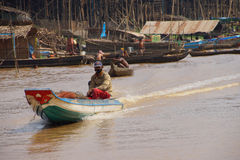 Power boat travels waterway. KOMPONG KLEANG, CAMBODIA - FEB 12, 2015 - Power boat travels along the waterway of Kompong Kleang floating fishing village, Cambodia royalty free stock images