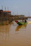 Power boat travels waterway. KOMPONG KLEANG, CAMBODIA - FEB 12, 2015 - Power boat travels along the waterway of Kompong Kleang floating fishing village, Cambodia royalty free stock photo