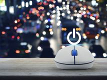 Start up business concept. Power button with wireless computer mouse on wooden table over blurred colourful night light city with cars, Start up business concept Royalty Free Stock Photography
