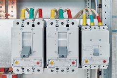 Power circuit breakers are arranged in a row in an electric Cabinet. royalty free stock image