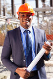 Power company manager. Handsome african power company manager standing in electrical substation royalty free stock photography