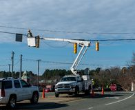 Power company worker repairing traffic light royalty free stock images