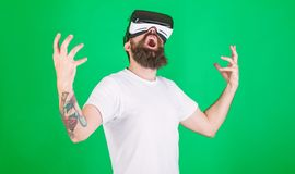 Power concept. Hipster on shouting face raising hands powerfully while interact in virtual reality. Man with beard in VR. Glasses, green background. Guy with stock photography