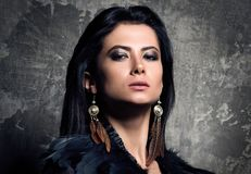 The power and confidence. Closeup portrait of young beautiful woman with dark hair. Dress and earrings with feathers. Light makeup and clean skin. Dark Stock Photos
