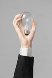 Power consumption and new business idea theme: man's hand in a black suit holding a light bulb on a gray background in studio Stock Photos