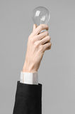 Power consumption and new business idea theme: man's hand in a black suit holding a light bulb on a gray background in studio Royalty Free Stock Photo