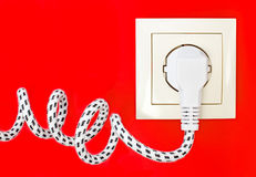 Power cord and power socket against a red background Royalty Free Stock Image