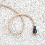 Power cord on carpet. Power cord with woven wire on carpet Royalty Free Stock Images