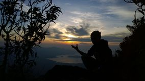 Power of dawn shadow. A man sitting on the summit of Kao Laem mt. watch the sun rising in his hand at Chang island, Thailand Stock Photos