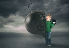 Power and determination of a child against a wrecking ball. Self confident child destroys a wrecking ball stock images