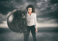 Power and determination of a young business woman against a wrecking ball. Self confident businesswoman destroys a wrecking ball stock image